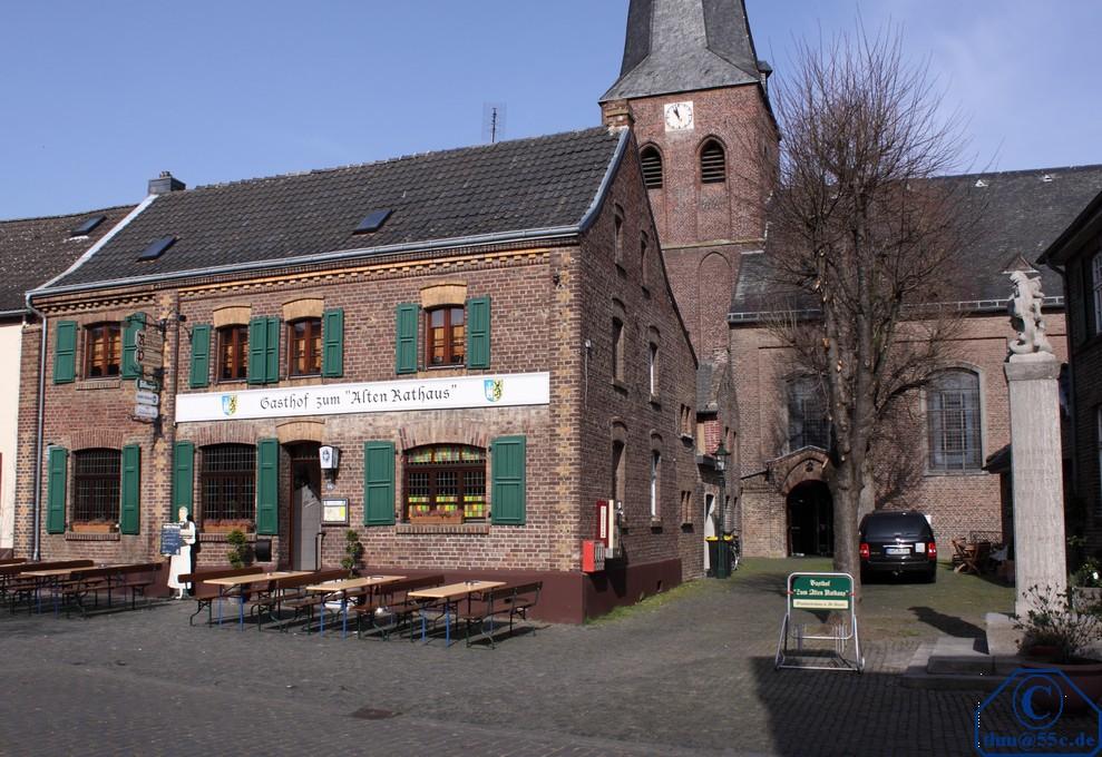 """Gasthof zum """"Alten Rathaus"""" in Alt-Kaster im Hintergrund die Kirche"""